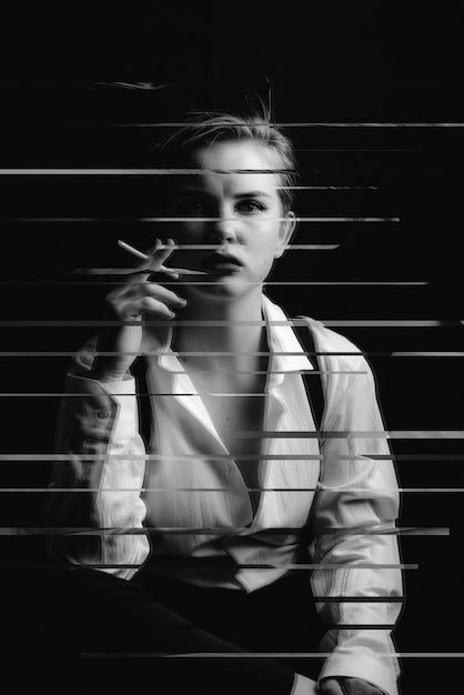 Schwarzweiss-foto eines mädchens, das eine zigarette raucht Premium Fotos
