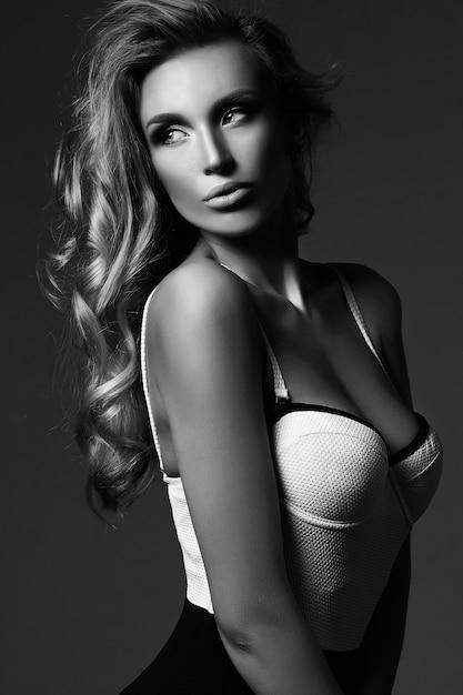 Schwarzweiss-porträt der schönen blonden frauenmodelldame des sinnlichen glamours mit frischem make-up und gesundem lockigem haar Kostenlose Fotos