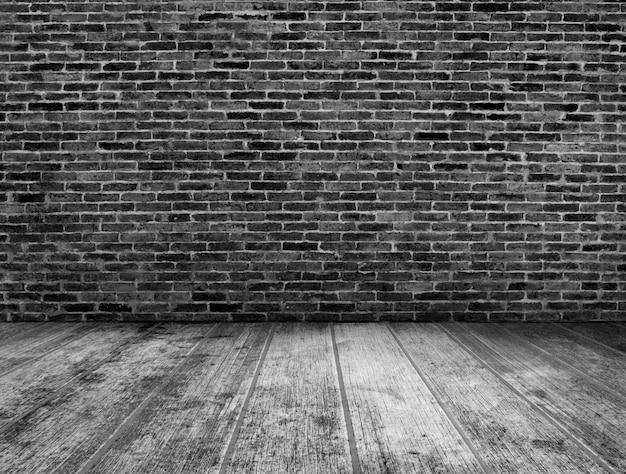 Schwarzweiss-schmutzrauminnenraum mit backsteinmauerhintergrund Premium Fotos