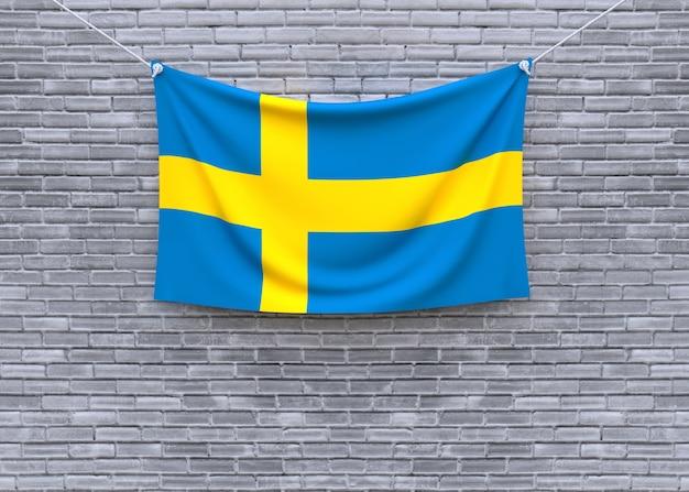 Schweden-flagge, die an der backsteinmauer hängt Premium Fotos