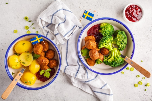 Schwedische fleischbällchen mit brokkoli, salzkartoffeln und preiselbeersoße. schwedisches traditionelles lebensmittelkonzept. Premium Fotos