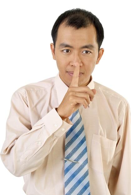 Schweigenzeichen mit asiatischem geschäftsmannfinger nahe lippen auf weißem hintergrund. Premium Fotos