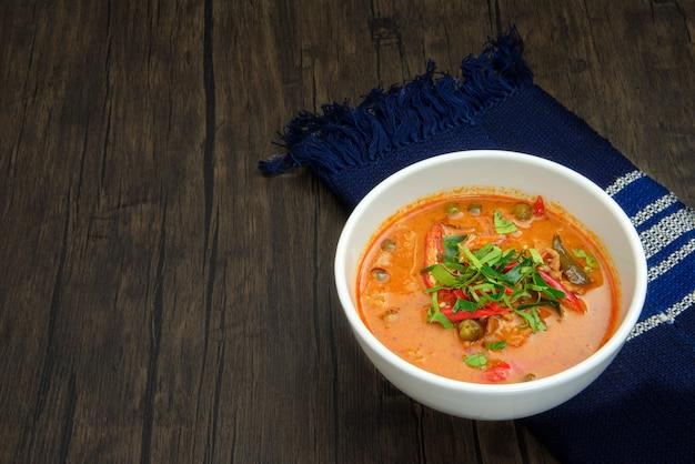 Schweinefleisch panang-curry in der weißen schüssel auf holzoberfläche mit kopienraum Premium Fotos