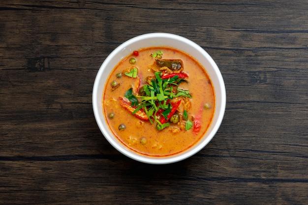 Schweinefleisch panang curry in der weißen schüssel auf holzoberfläche Premium Fotos