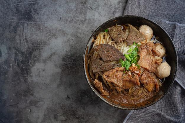 Schweinefleischbootnudeln, klassisches thailändisches essen und beliebte menüs sowie verzehrfertige suppen. es gibt auch ein basilikum in der schüssel. Kostenlose Fotos