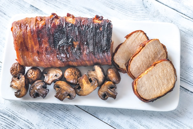 Schweinelende in speck mit gerösteten pilzen gewickelt Premium Fotos