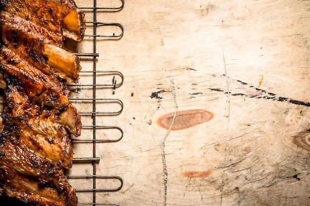 Schweinerippchen auf dem grill gegrillt. auf holztisch. Premium Fotos
