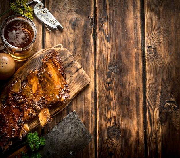 Schweinerippchen gegrillt mit einem fleischbeil und bier auf holztisch. Premium Fotos