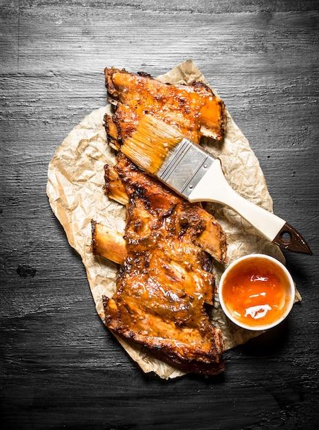 Schweinerippchen mit einer würzigen sauce und einem pinsel gegrillt. auf der schwarzen kreidetafel Premium Fotos
