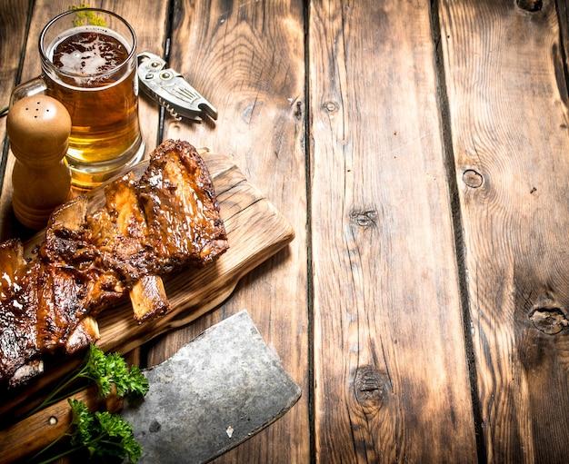 Schweinerippchen mit fleischbeil und bier gegrillt. auf einem holztisch. Premium Fotos