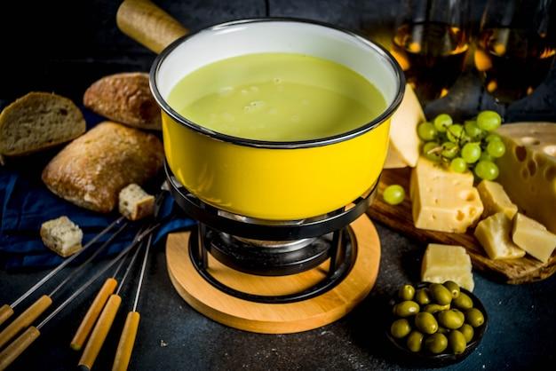 Schweizer feinschmeckerfondue im traditionellen fonduetopf mit gabeln, verschiedenen käsesorten, oliven, brot und trauben Premium Fotos