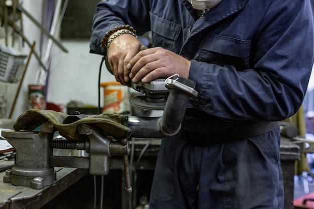 Schwerindustriearbeiter, der stahl mit winkelschleifer am autoservice schneidet. Premium Fotos