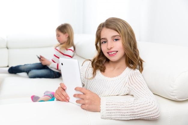 Schwester freunde kinder mädchen spielen mit tablet pc im sofa Premium Fotos