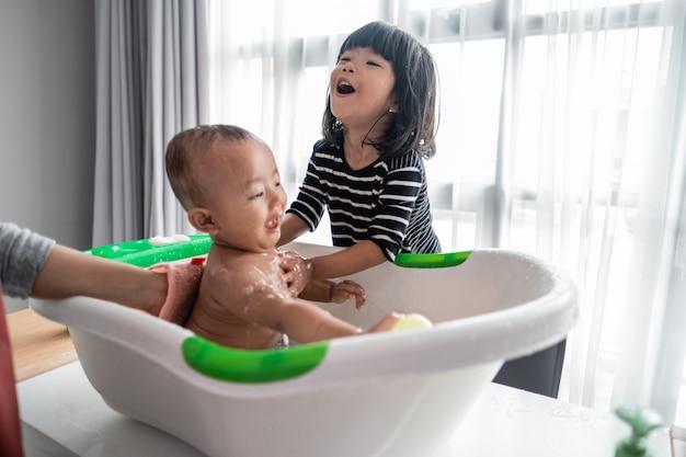 Schwester hilft ihrem kleinen bruder beim baden | Premium-Foto