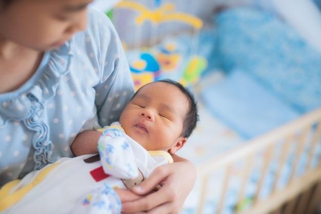 Schwester holt asiatischen neugeborenen bruder zum schlafen Premium Fotos