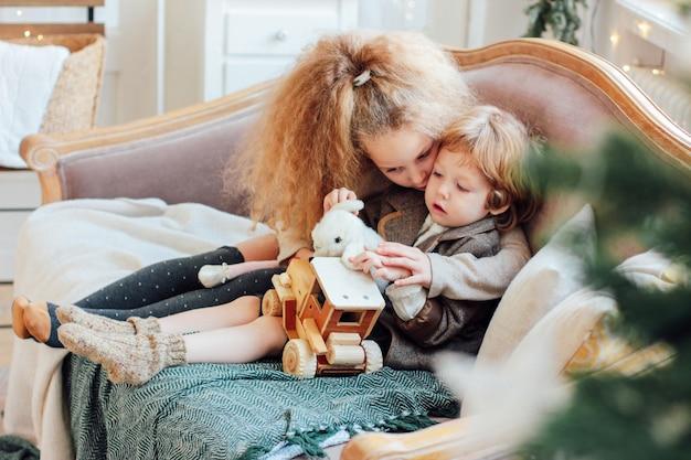 Schwester umarmt kleinen bruder auf der couch, gemütlicher wintertag Premium Fotos