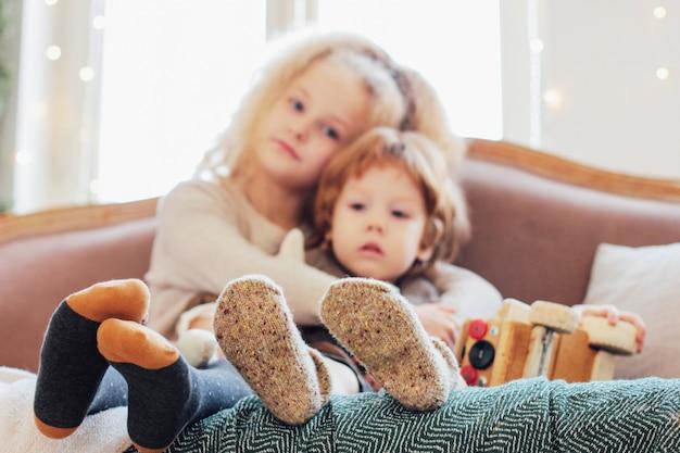 Schwester umarmt kleinen bruder auf der couch, konzentriert sich auf die beine in warmen s Premium Fotos