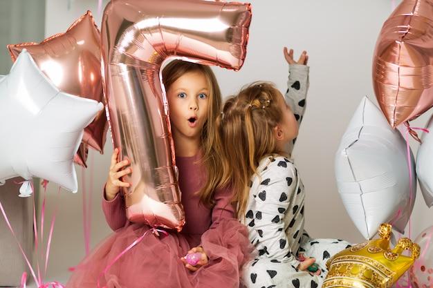 Schwestern spielen mit luftballons Premium Fotos