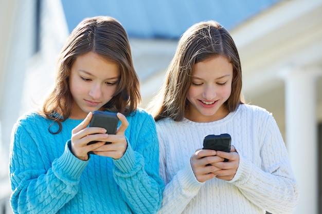 Schwesterzwillinge, die spaß mit technologie smartphone haben Premium Fotos