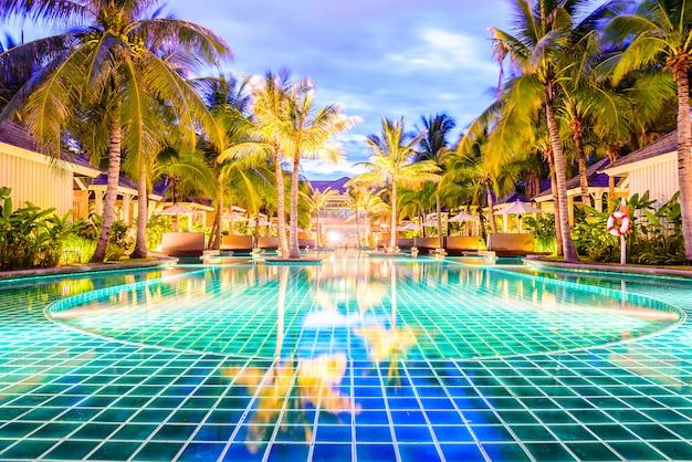 Schwimmbad mit palmen im urlaubshotel in der nacht Kostenlose Fotos