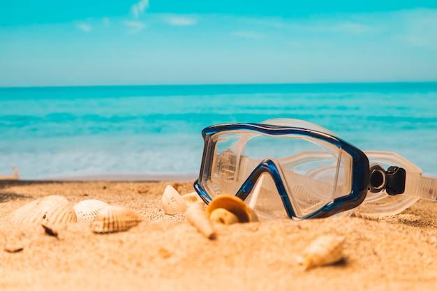 Schwimmbrille am sandstrand Premium Fotos