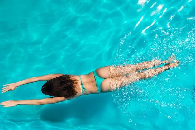 Schwimmen der erwachsenen frau unter hellem klarem wasser Kostenlose Fotos