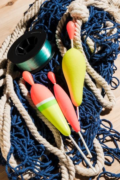 Schwimmer und angelrolle auf blauem fischernetz Kostenlose Fotos