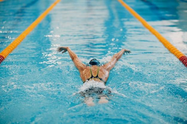 Schwimmerin der jungen frau schwimmt im schwimmbad Premium Fotos