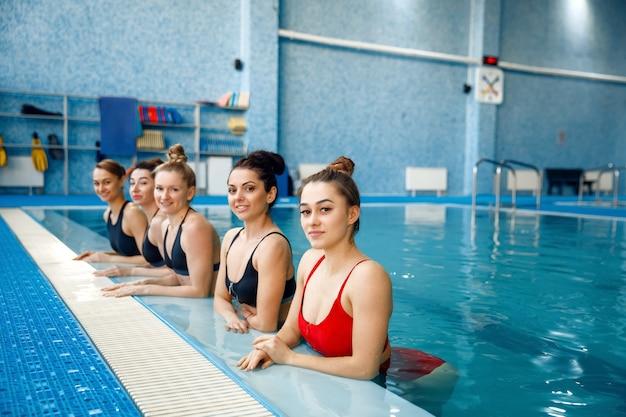 Schwimmerinnen posieren am pool. frauen fit training im wasser, sportschwimmen, fitness-training im pool Premium Fotos