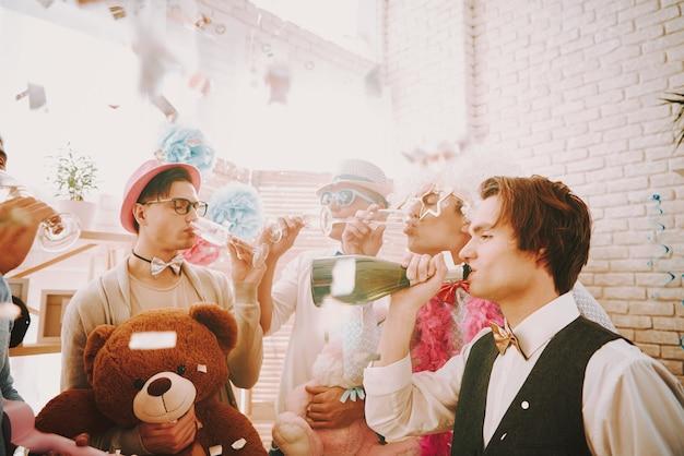 Schwule trinken champagner und entspannen sich bei einer schwulenparty. Premium Fotos