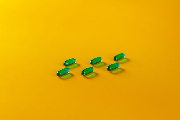 Sechs grüne transparente pillen auf einem gelb. gesundheit. gesunder lebensstil . das konzept der pharmakologie. das konzept der medizin. das konzept der medizinischen instrumente. Premium Fotos