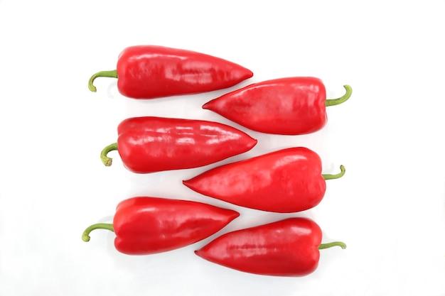 Sechs leuchtend rote paprika auf einem weißen Premium Fotos