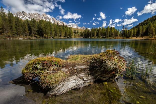 See umgeben von felsen und wäldern mit bäumen, die auf dem wasser unter dem sonnenlicht in italien reflektieren Kostenlose Fotos