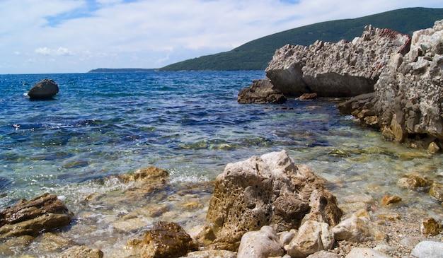 Seeansicht mit felsen und bewölktem himmel, stadt montenegros, perast Premium Fotos