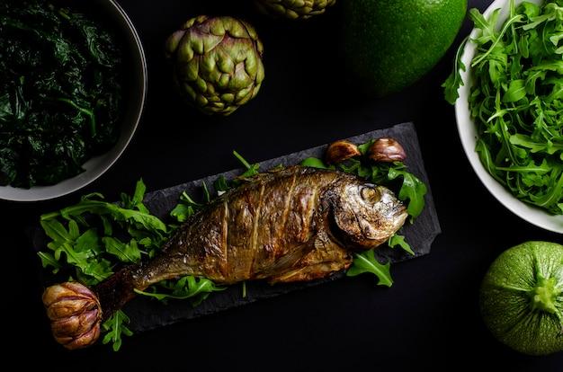 Seebrassen backten im ofen auf schwarzer umhüllungsplatte mit arugula und grünem gemüse auf schwarzem hintergrund Premium Fotos