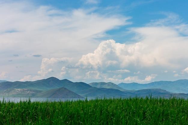 Seelandschaft mit mountines und stöcken, blauer himmel mit wolken, wolkig ohne sonne, kasachstan Premium Fotos