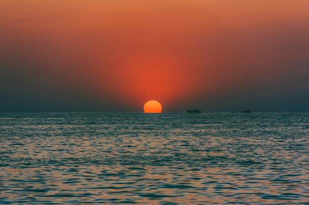 Seelandschaft mit untergehender sonne und schiffen Premium Fotos