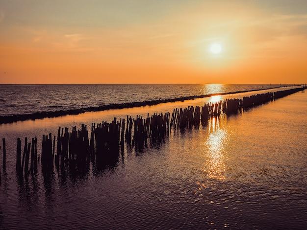 Seesonnenuntergangansicht von kleinem hölzernem am horizont mit leuteschattenbild und orange himmellandschaft. Premium Fotos