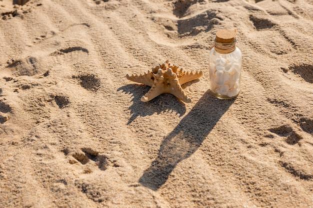 Seestern und glas mit muscheln am sandstrand Kostenlose Fotos