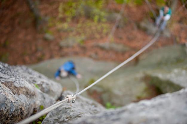 Sehen sie das hängen des bergsteigerkarabiners und -seils auf dem felsen an Premium Fotos