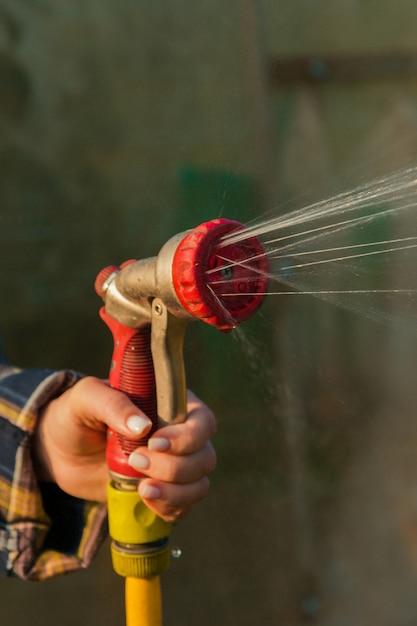Sehen sie die frauenhände an, die pflanzen vom schlauch gießen, macht einen regen im garten. gärtner mit gießschlauch und sprühwasser auf den blumen. Premium Fotos