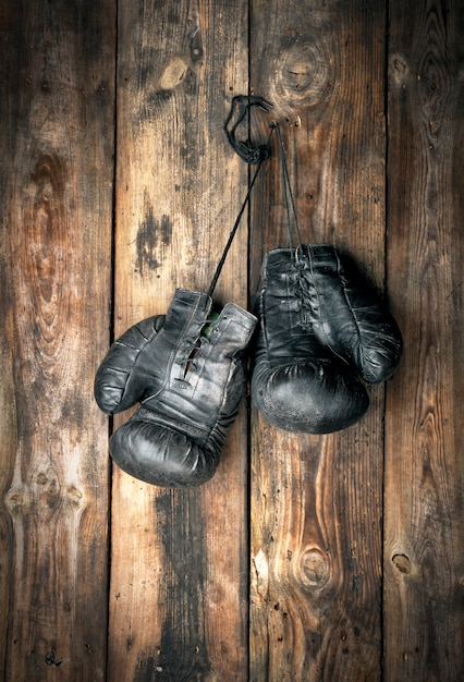Sehr alte schwarze boxhandschuhe aus leder hängen Premium Fotos