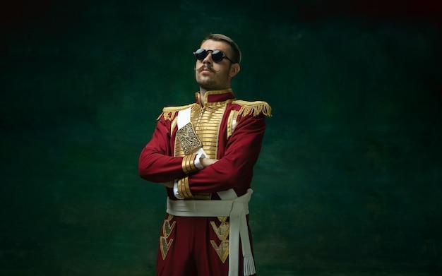 Sehr ernst. junger mann im anzug als nikolaus ii. auf dunkelgrün isoliert Kostenlose Fotos