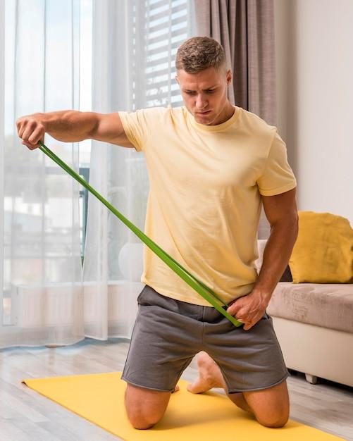 Sehr fitter mann, der zu hause mit gummiband trainiert Kostenlose Fotos