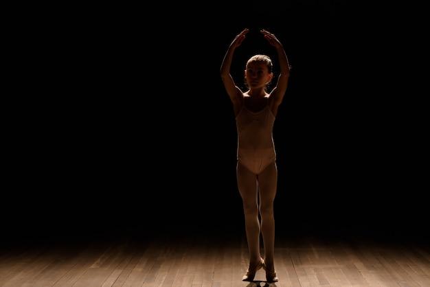 Sehr junge ballerina, die auf einem schwarzen hintergrund aufwirft Premium Fotos