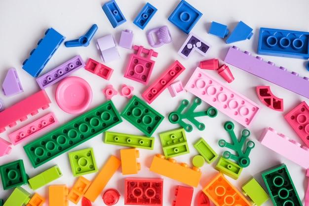Sehr viele kinderspielzeuge. flach liegend. spiel für die kindertagesstätte, vorschule. kindergarten-lernspiele. die farben des regenbogens. bunte plastikspielwaren in der verschiedenen form. Premium Fotos