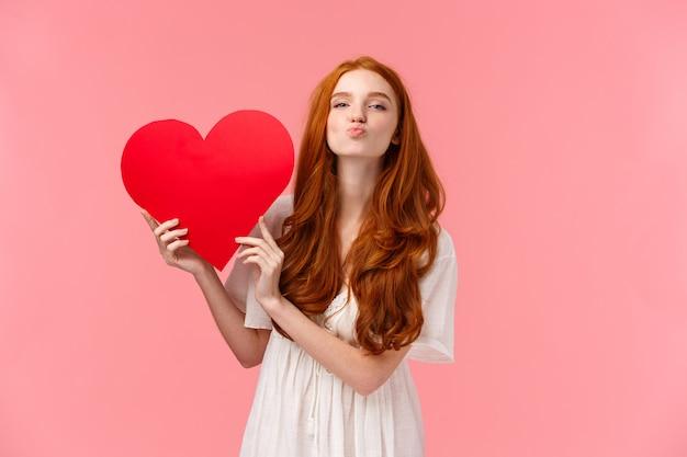 Sei mein valentinsschatz. die reizende und sinnliche, zarte rothaarigefreundin, die liebe und sorgfalt ausdrückt, glückwunsch mit dem valentinstag, großes rotes herz zeigend, faltenlippen senden luftkuss an, rosa wand Premium Fotos