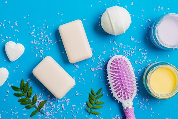 Seife; badebombe; feuchtigkeitscreme creme und haarbürste auf blauem hintergrund Kostenlose Fotos