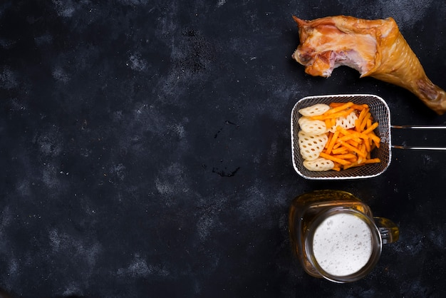 Seite eines glases bieres, der imbisse und des geräucherten hühnerbeins auf einem schwarzen hintergrund Premium Fotos