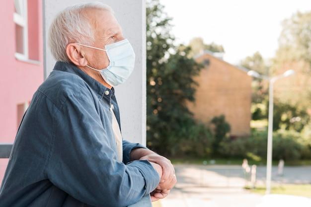 Seitenansicht alter mann, der medizinische maske trägt Premium Fotos